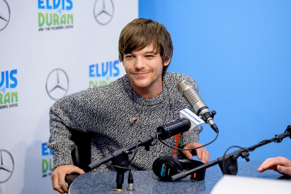 Louis Tomlinson grins in a grey sweater at the Elvin Duran morning shown
