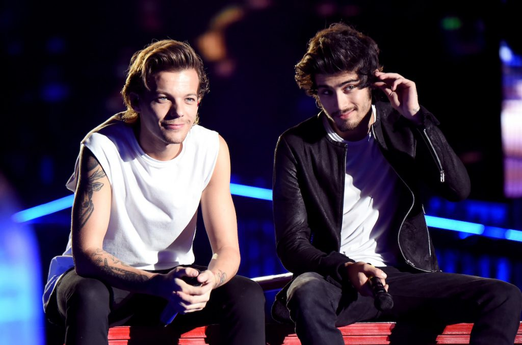 Louis Tomlinson and Zayn Malik sit down on stage during One Direction tour