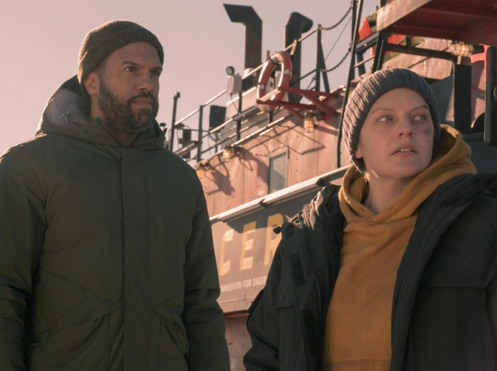 O-T Fagbenle as Luke wearing a green winter coat and beanie, and Elisabeth Moss as June wearing a yellow hoodie, green winter coat, and grey beanie as they stand in front of a boat in 'The Handmaid's Tale' Season 4.