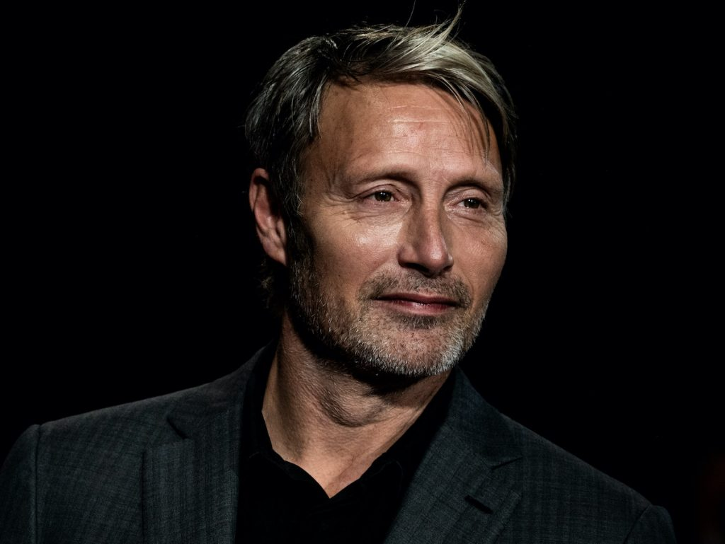 Mads Mikkelsen in a dark grey suit and black shirt in front of a black background