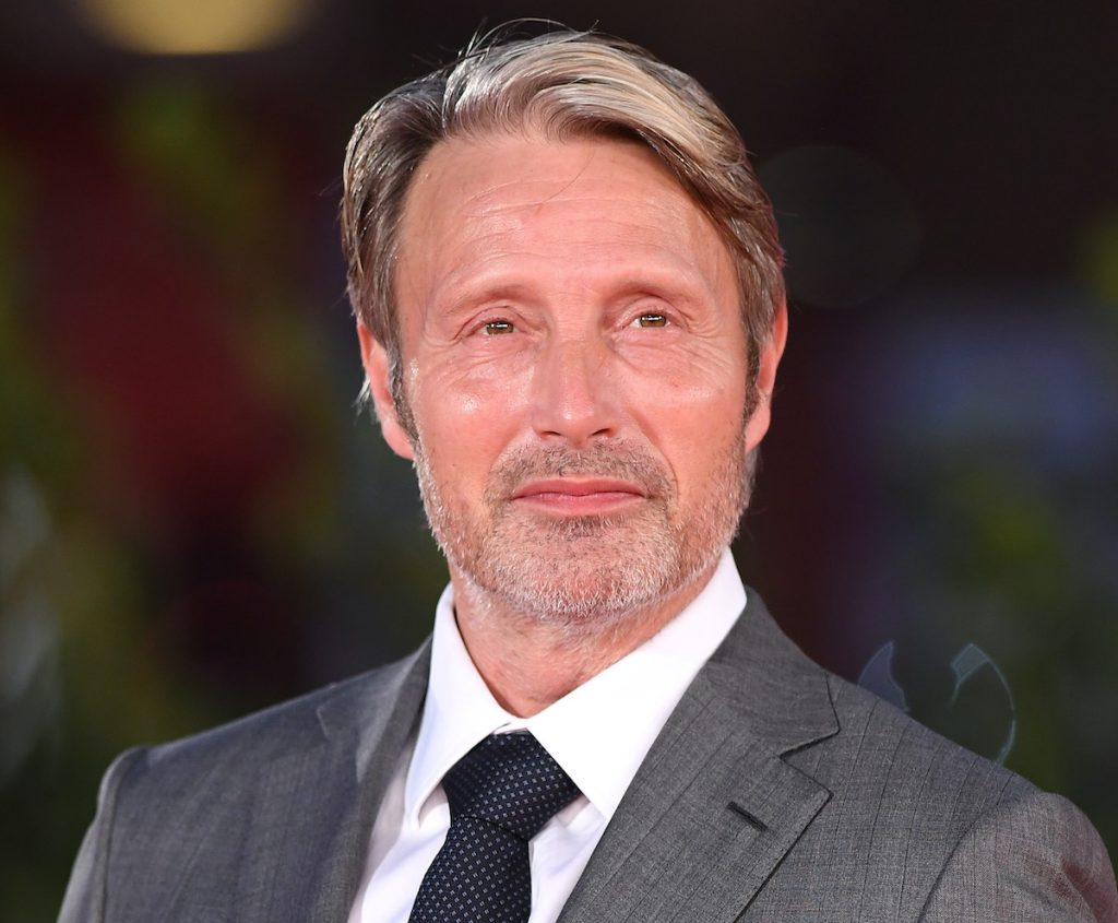 Mads Mikkelsen in a grey suit and navy blue tie