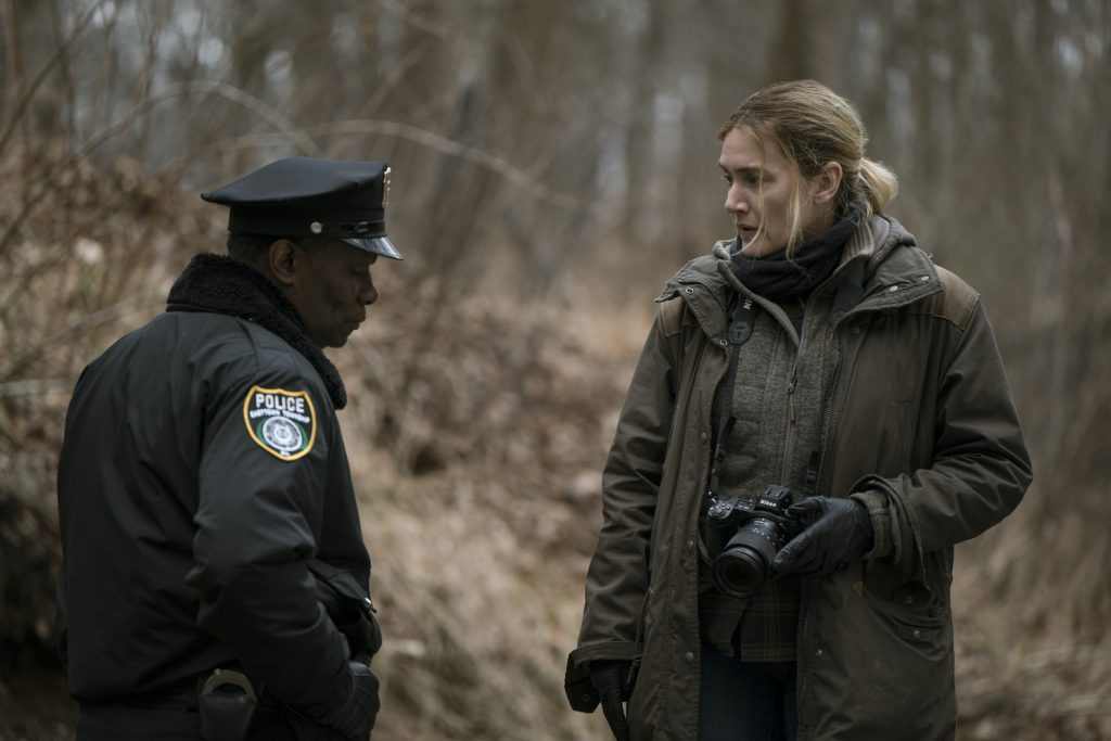 Kate Winslet plays small-town detective Mare who is talking to John Douglas Carter who plays Chief Carter as they investigate a murder in the woods on a dreary day in Easttown.