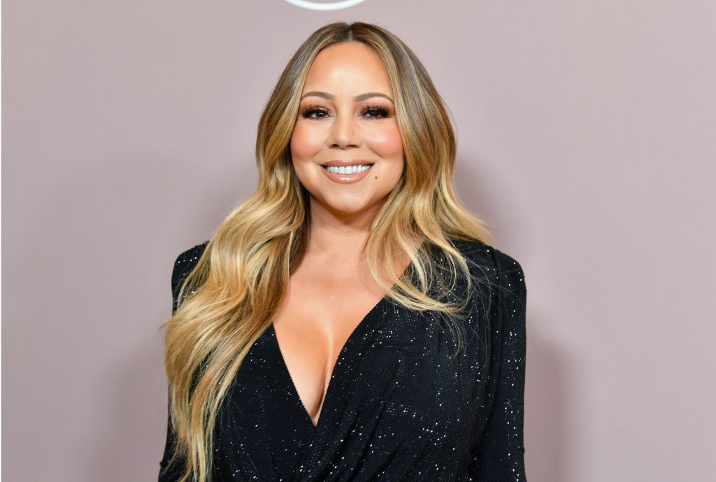 Mariah Carey smiling in front of a pink background
