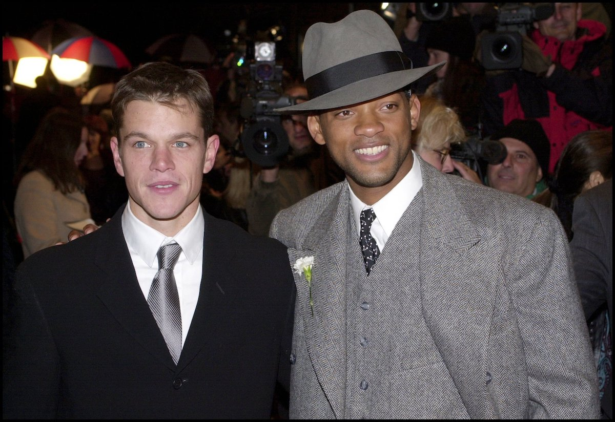 Matt Damon in a black suit and silver tie poses with Will Smith in a grey suit and hat at the premiere of 'The Legend of Bagger Vance'