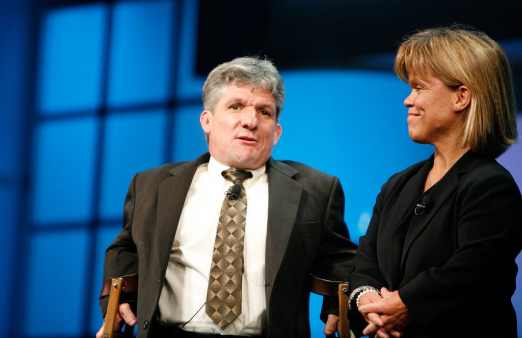 Matt and Amy Roloff, parents of Zach, Jeremy, Molly, and Jacob Roloff, of 'Little People, Big World' standing together against a blue background