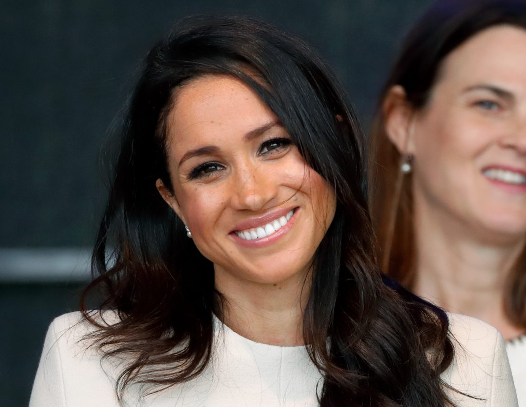 Photo of Meghan Markle from the shoulders up with her hair down and smiling for a photo