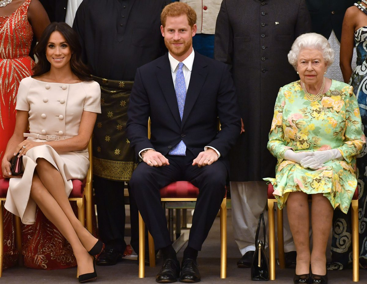 Meghan Markle, Prince Harry, and Queen Elizabeth II seated next to one another and posing for a photo at the Queen's Young Leaders Awards Ceremony