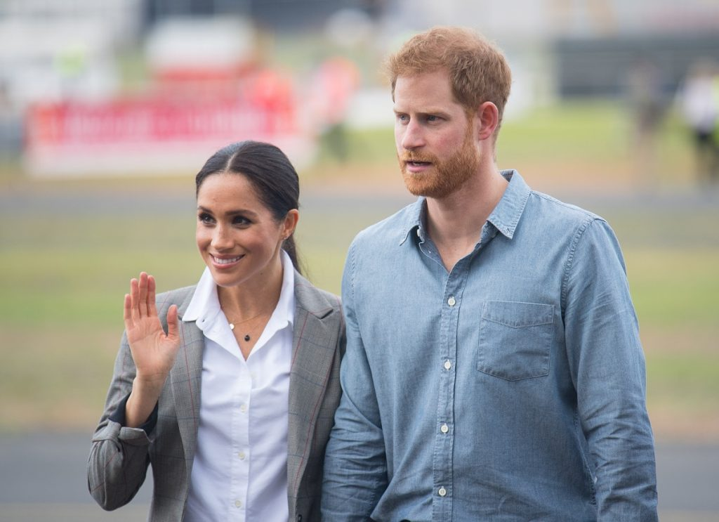Meghan Markle giving a wave at airport in Australia with Prince Harry