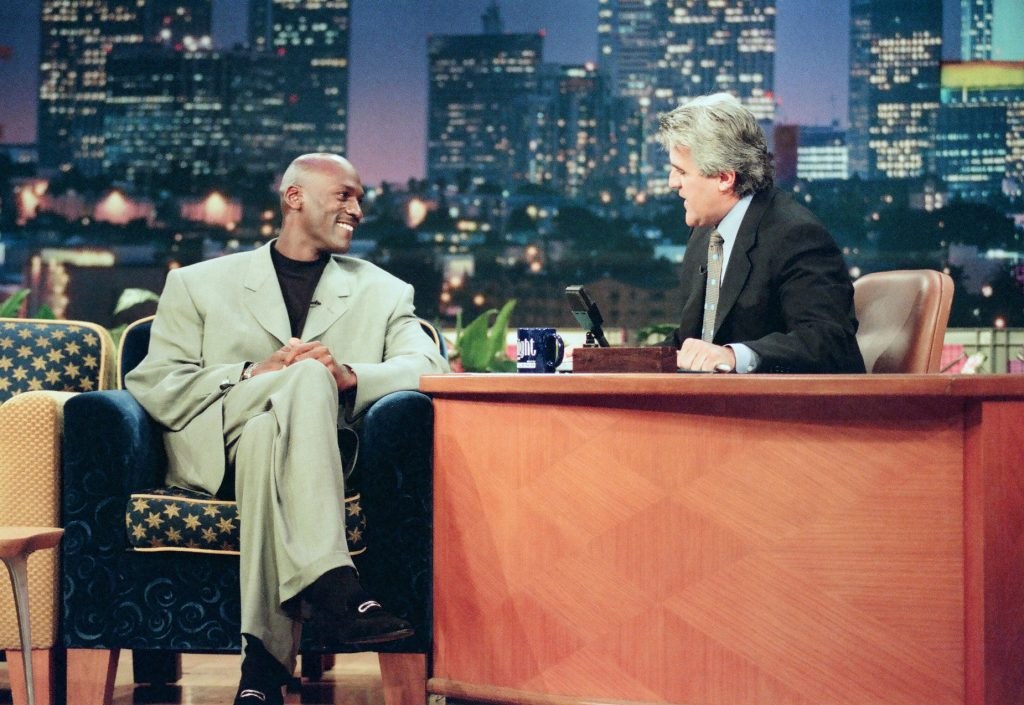 Michael Jordan wears one of his signature baggy suits while being interviewed by Jay Leno.