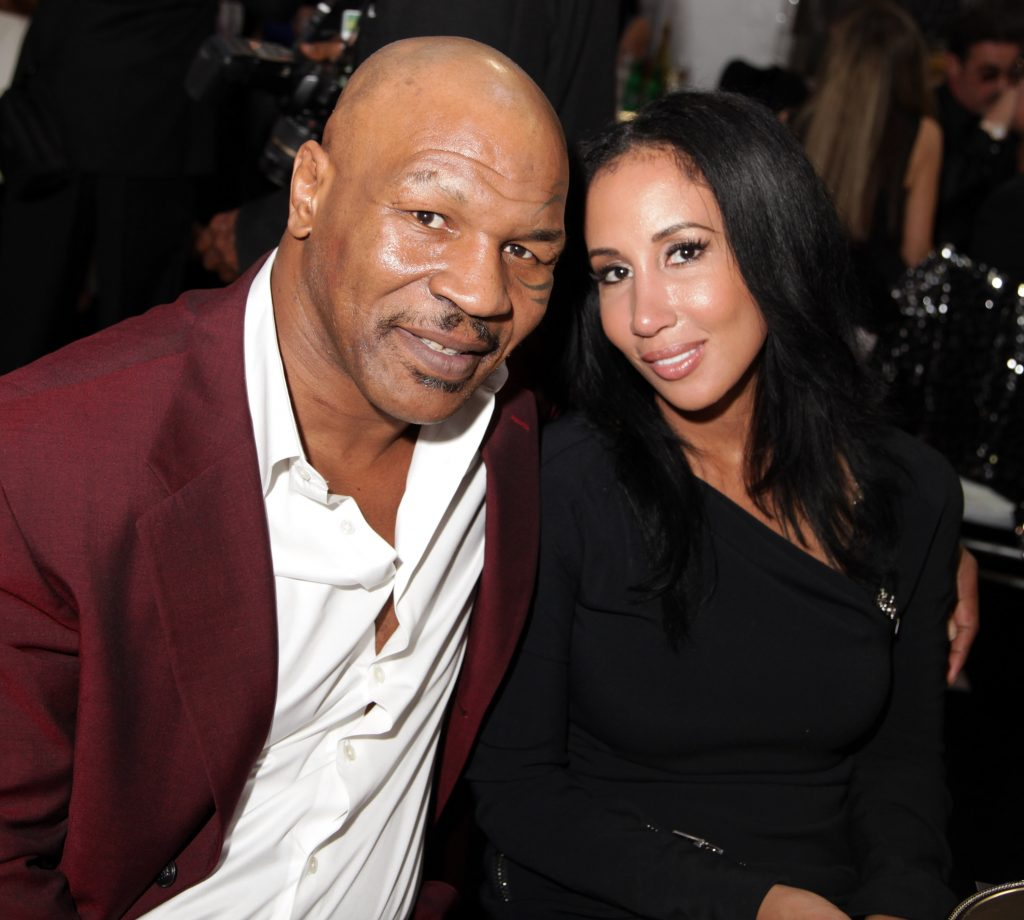 Mike Tyson and his wife Lakiha 'Kiki' Spicer seated next to each other and posing for a photo at Academy Awards Viewing Party Benefiting Children Uniting Nations