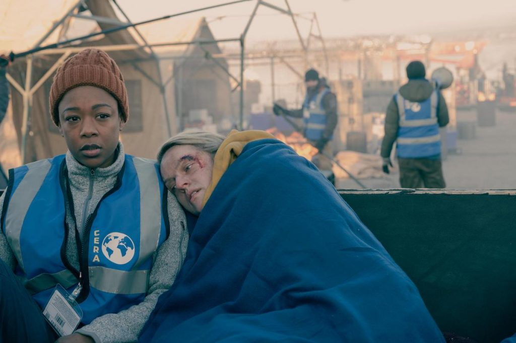 Samira Wiley as Moira in a blue vest, orange beanie, and light grey zip-up turtleneck sweater. Elisabeth Moss as June lays her head on Wiley's shoulder wearing a yellow hoodie and wrapped in a blue blanket. From season 4 of 'The Handmaid's Tale.'