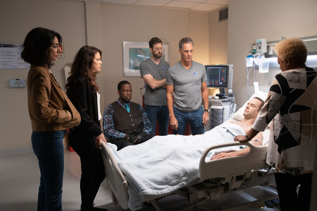 Necar Zadegan as Special Agent Hannah Khoury, Vanessa Ferlito as FBI Special Agent Tammy Gregorio, Daryl Chill Mitchell as Patton Plame, Rob Kerkovich as Forensic Scientist Sebastian Lund, Scott Bakula as Special Agent Dwayne Pride, and CCH Pounder as Dr. Loretta Wade stand over Christopher La Salle played by Lucas Black as he lies in a hospital bed, unconscious.