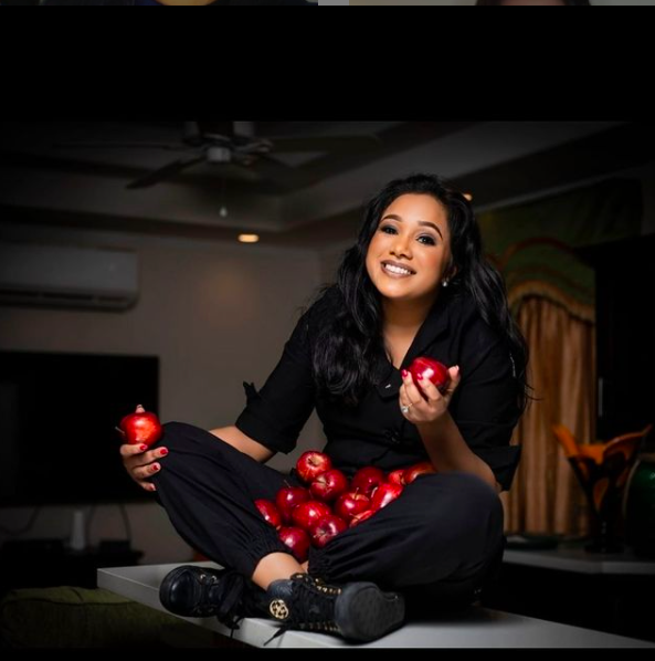 Chef Natasha de Bourg poses with apples while sitting on a table.