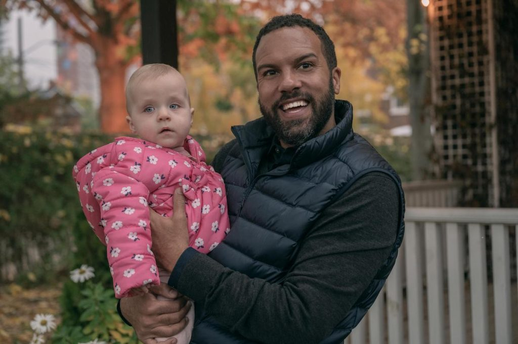 O-T Fagbenle as Luke in 'The Handmaid's Tale' holding baby Nicole. He's smiling and wearing a black shirt and puffer vest. Nicole wears a pink jacket.