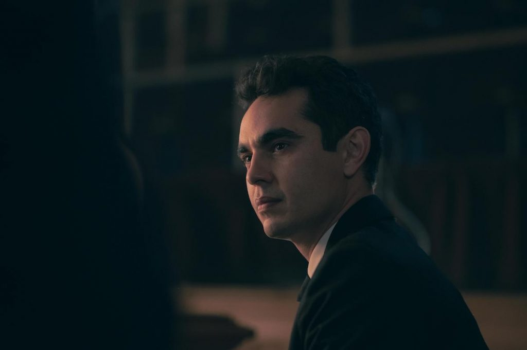 Max Minghella in a black suit and white shirt looking stern in a darkly lit room as Nick in 'The Handmaid's Tale' Season 4.