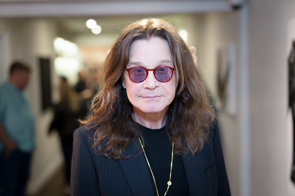 Ozzy Osbourne smiling in front of a blurred background