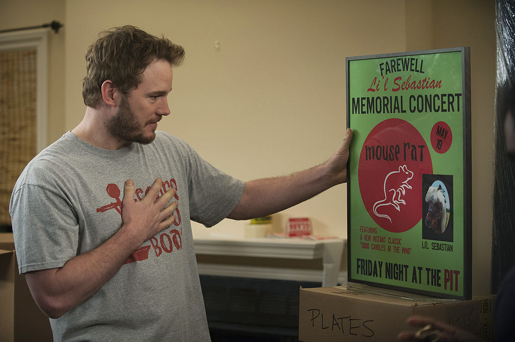 Chris Pratt as Andy Dwyer, dressed in a grey t-shirt, looks at a green and red poster for a Mouse Rat concert.