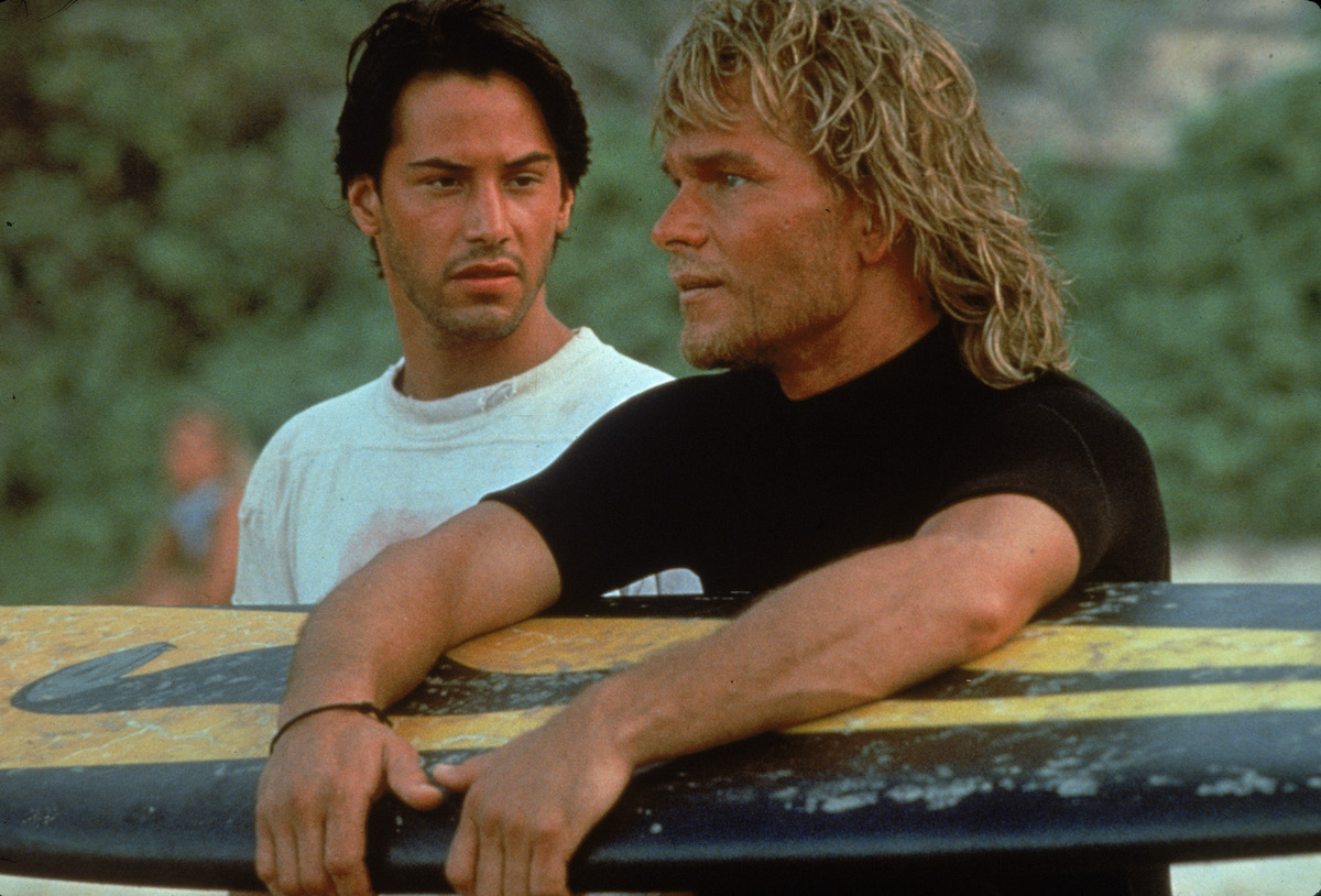 Keanu Reeves and American actor Patrick Swayze stand on a beach as Swayze holds a surfboard in 'Point Break'