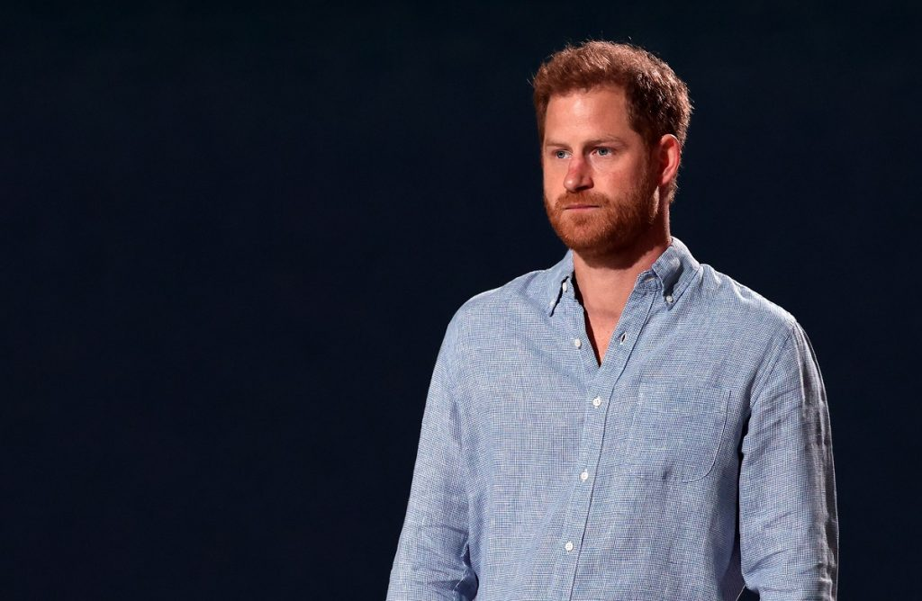 Prince Harry in a light blue shirt against a dark background
