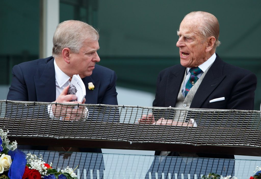 Prince Philip speaking to his son, Prince Andrew, on the balcony of the Royal Box during Derby Day