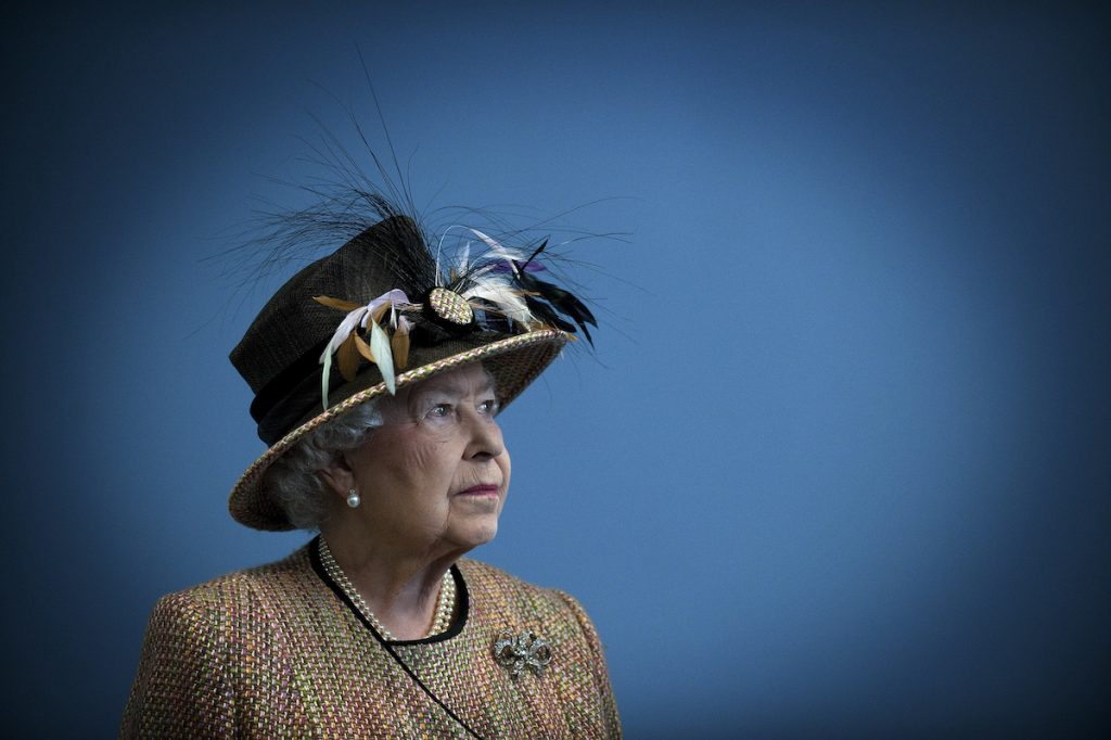 Queen Elizabeth looks to the side wearing a large hat