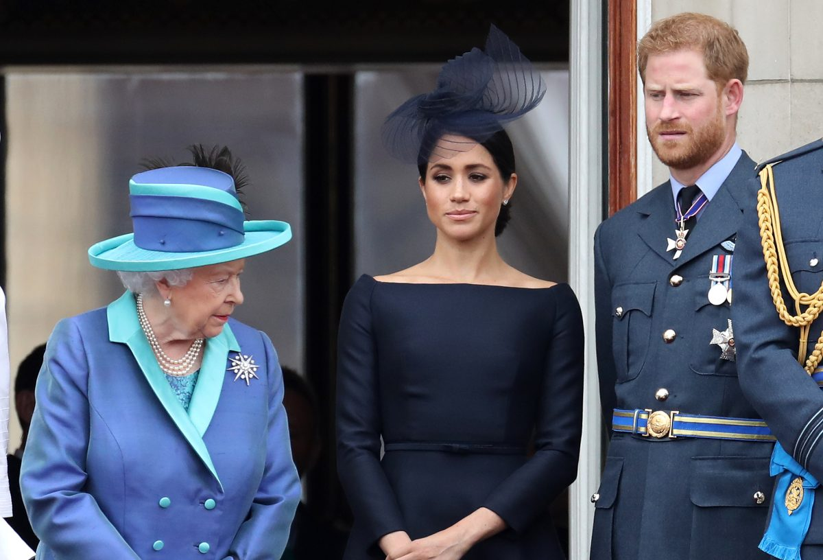 Queen Elizabeth II, Prince Harry, and Meghan Markle standing on the balcony of Buckingham Palace