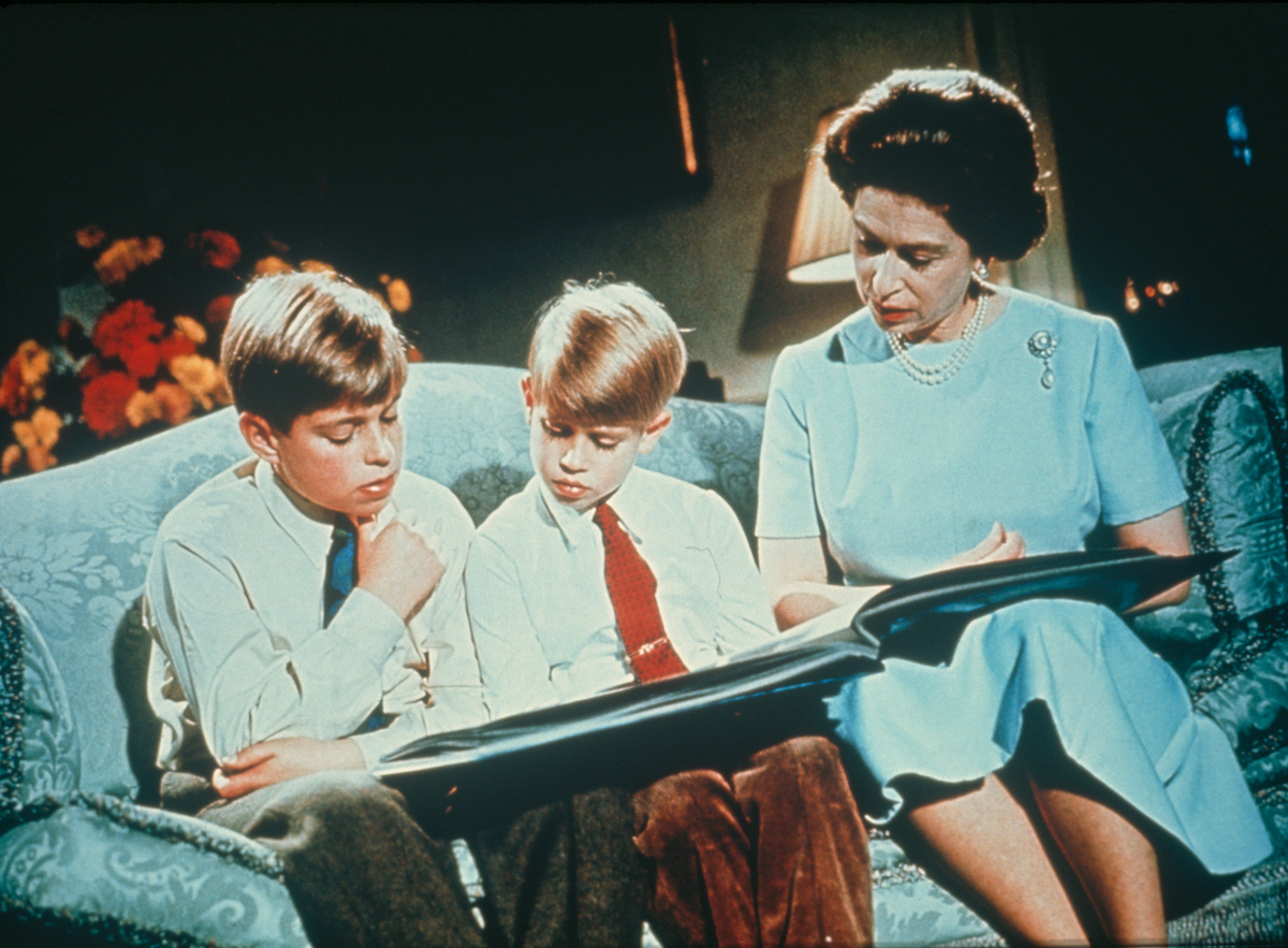 Queen Elizabeth looking at a photo album with Prince Andrew and Prince Edward