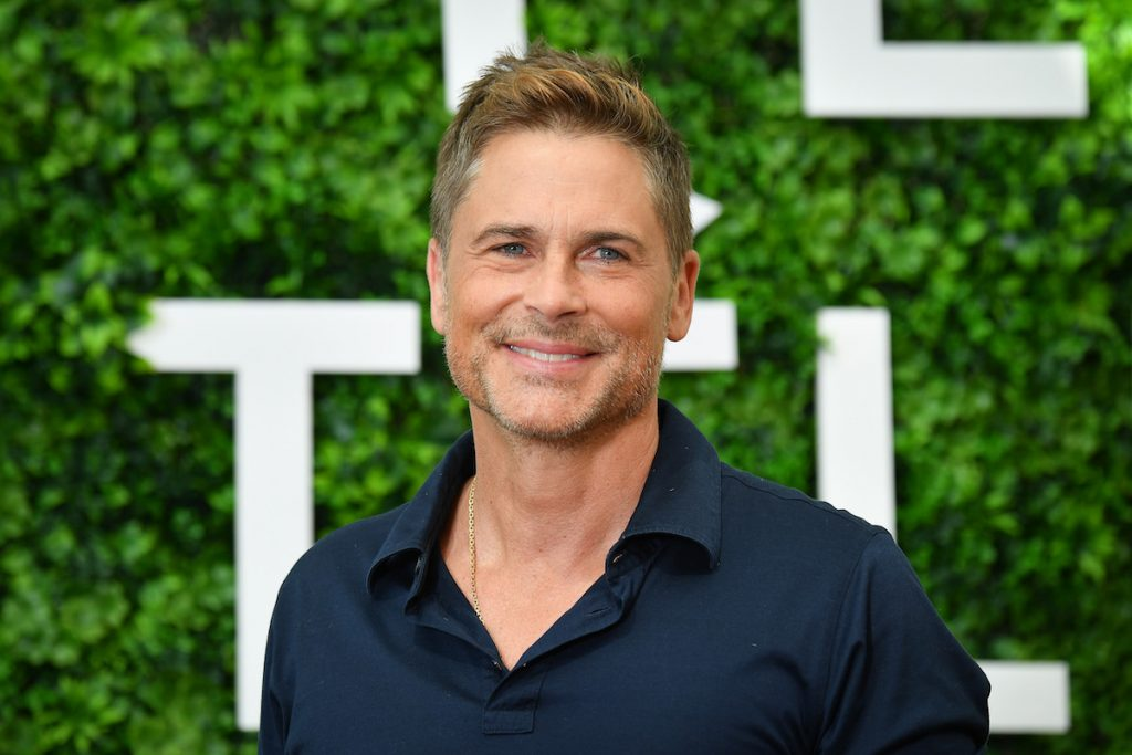 Rob Lowe smiles while wearing a blue shirt