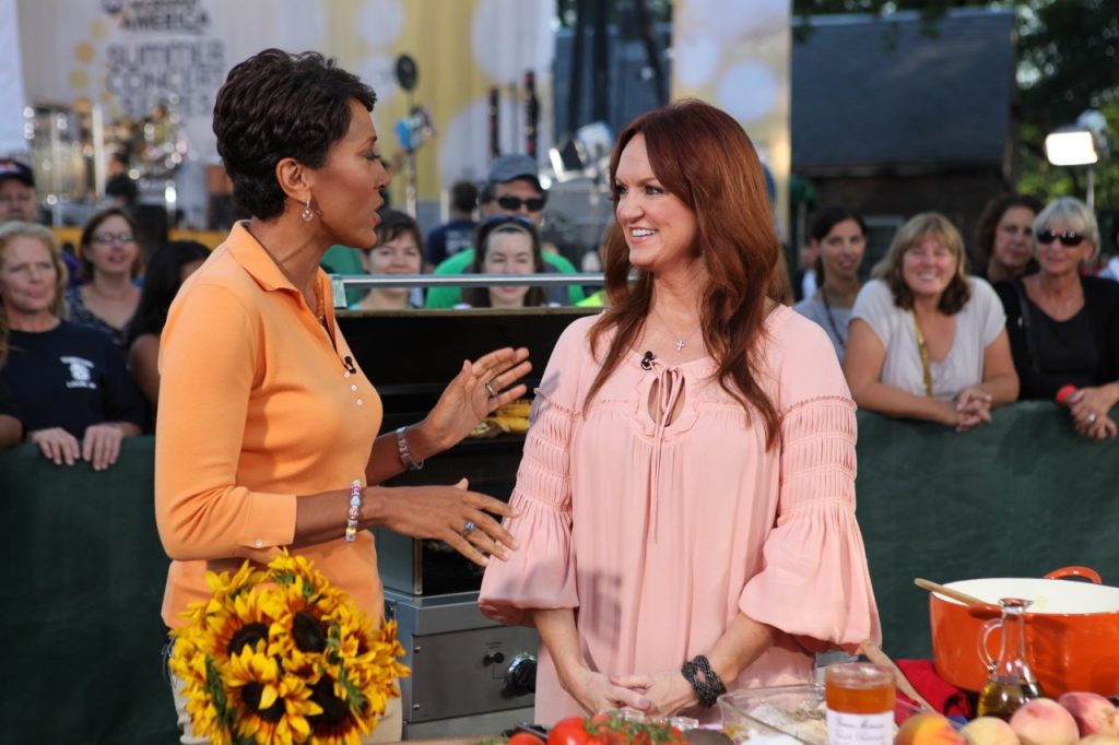 Robin Roberts is wearing an orange shirt and is talking to Ree Drummond, who is wearing a pink shirt and is smiling