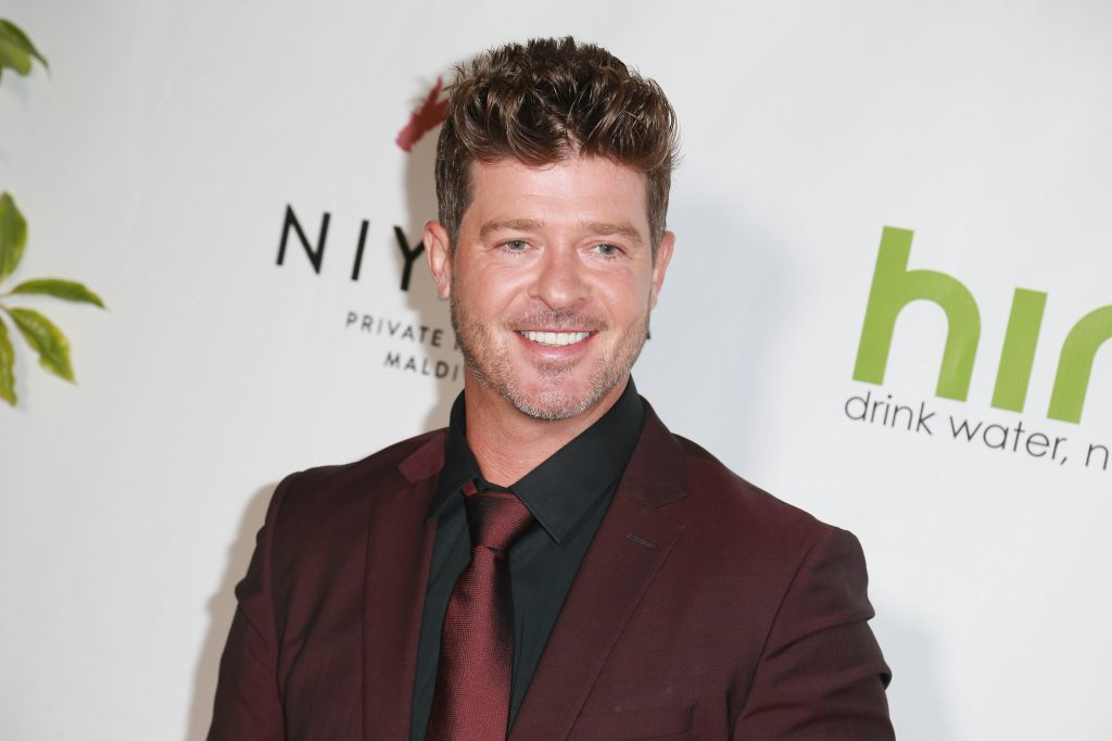 Robin Thicke smiling in front of a white background