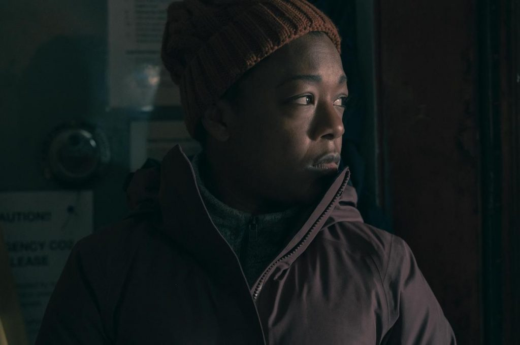 Samira Wiley in a brown coat and beanie looking out a window on a boat in 'The Handmaid's Tale' Season 4