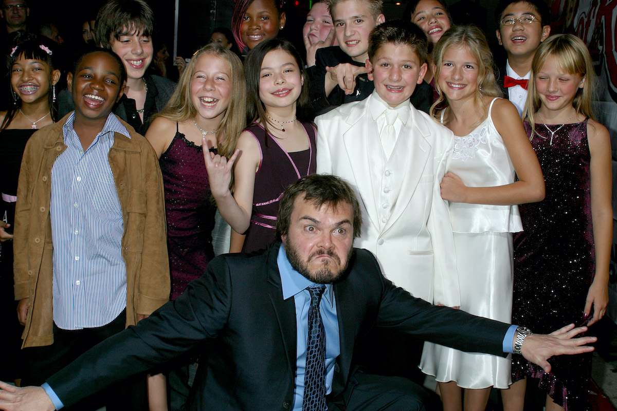 Jack Black poses wildly with his arms outstretched in front of the child actor stars of 'School of Rock'