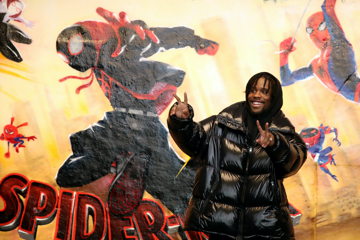 A smiling Shameik Moore poses at an event for 'Spider-Man: Into the Spider-Verse' in 2018
