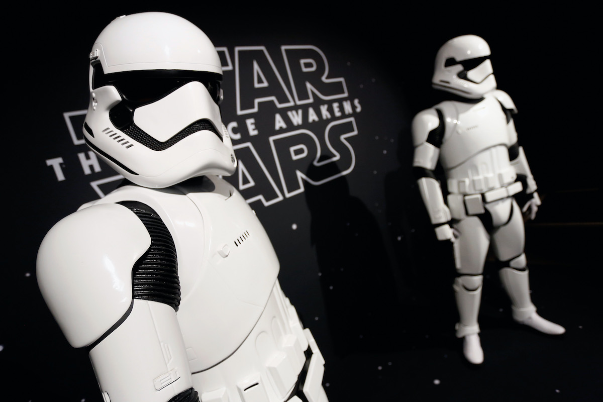 Two stormtroopers stand in front of the 'Star Wars: The Force Awakens' logo at the Star Wars 'Force 4 Fashion' event