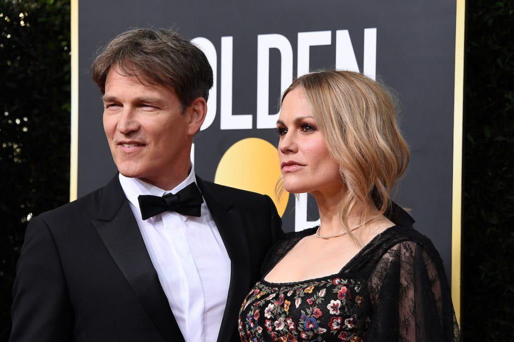 Stephen Moyer is in a tux and Anna Paquin is in a black floral dress on the red carpet.