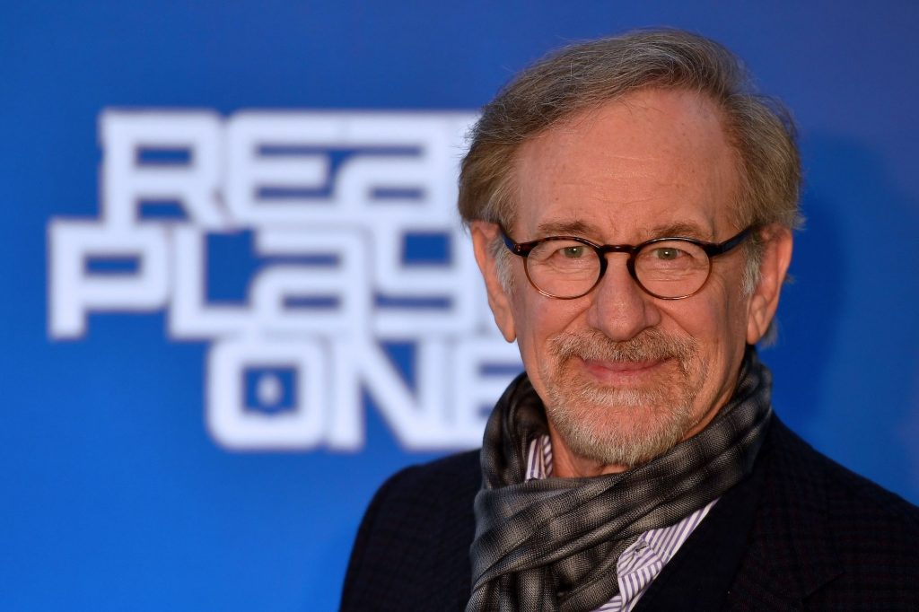 Steven Spielberg smiling in front of a blue background