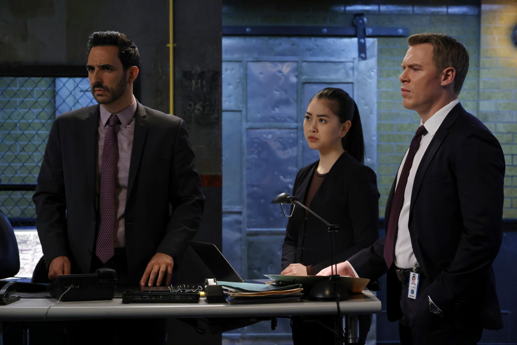Amir Arison as Aram Mojtabai is dressed in a suit next to Laura Sohn as Agent Alina Park in all black, and Diego Klattenhoff as Donald Ressler in a suit. They all look concerned.