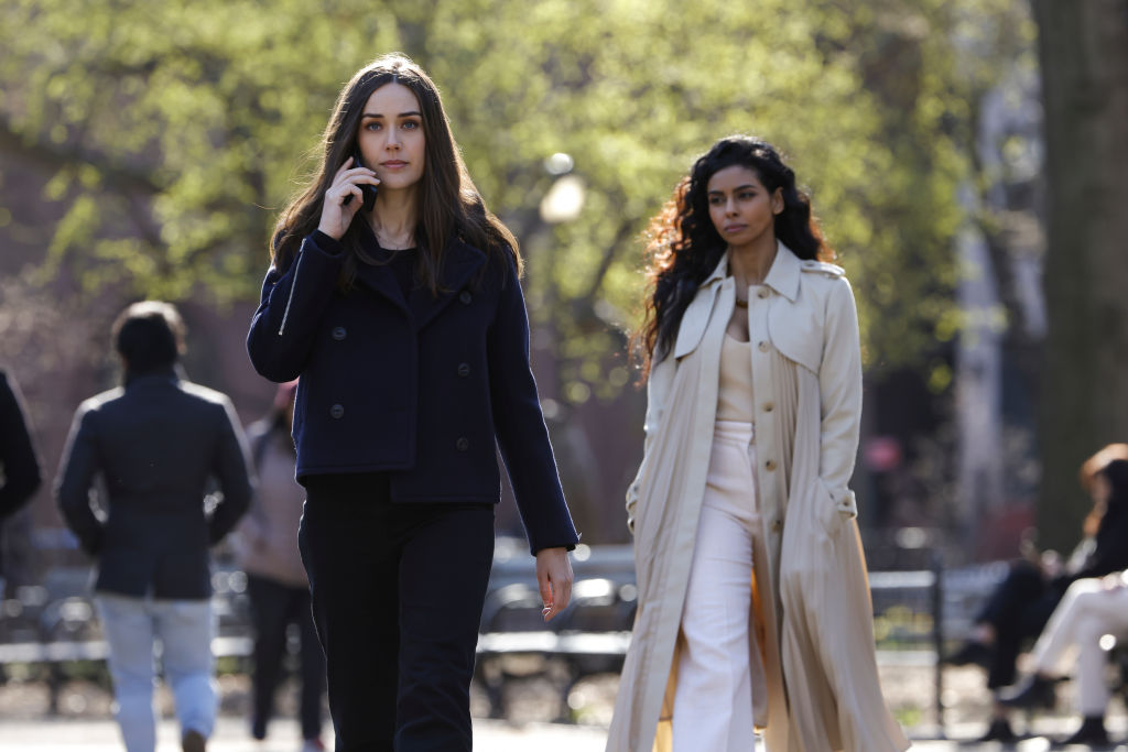 Megan Boone as Liz Keen walks as she talks on the phone. She is dressed in dark clothing while Rana Roy as Priya Laghari follows, dressed in ivory.