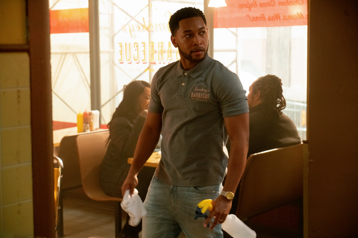 Jacob Latimore as Emmett standing in a restaurant in The Chi