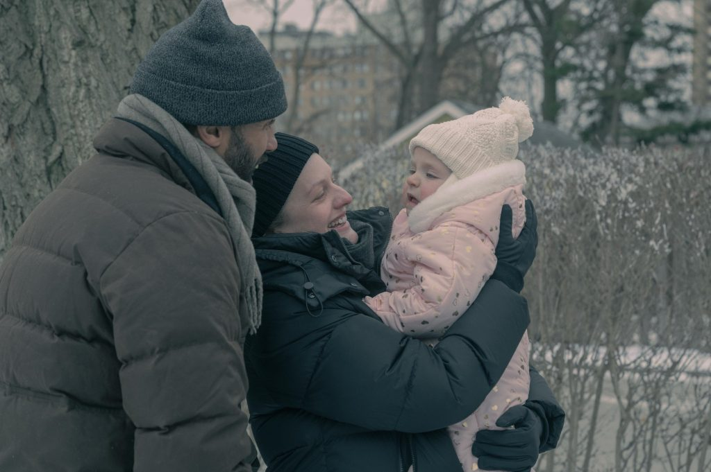 Luke (O-T Fagbenle) and June (Elisabeth Moss) play with Nichole in the snow in 'The Handmaid's Tale'