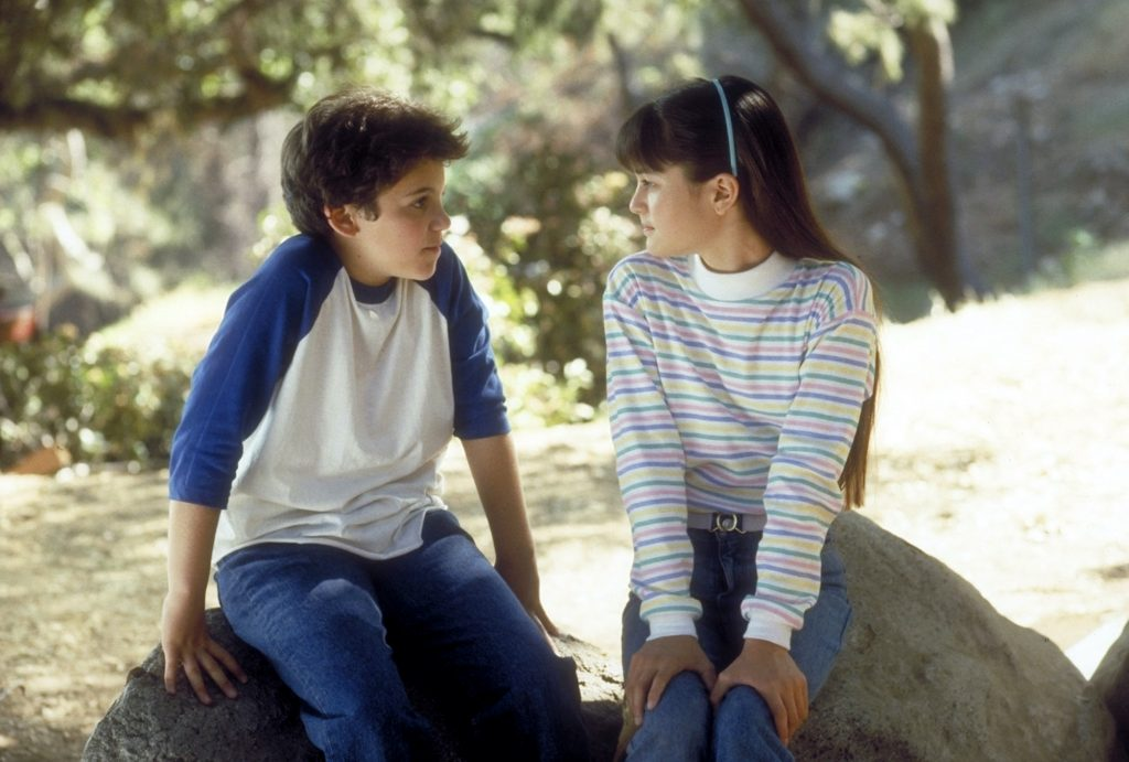 Fred Savage and Danica McKellar facing each other, sitting on rocks