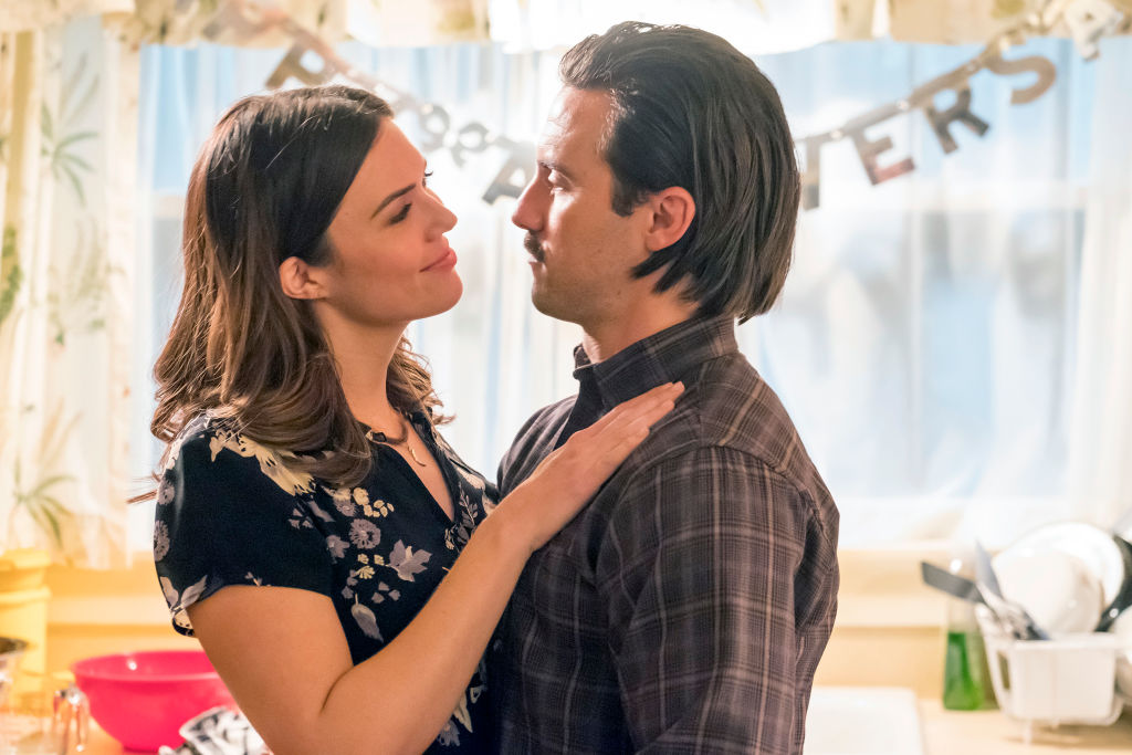 Mandy Moore as Rebecca, Milo Ventimiglia as Jack look loving at one another while standing in the kitchen.