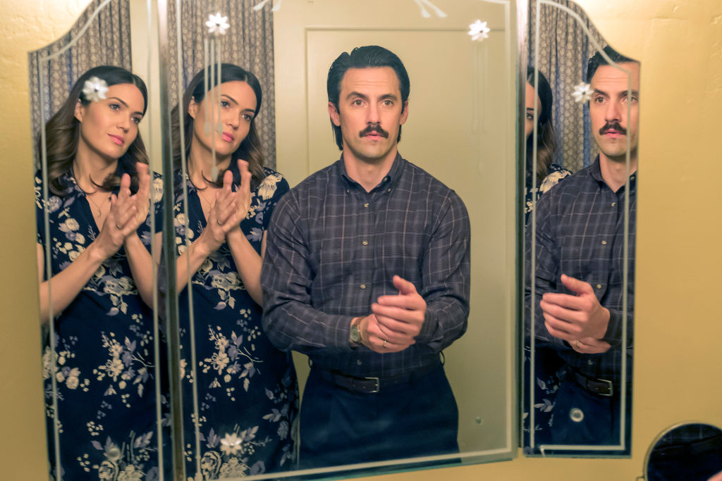 Mandy Moore as Rebecca looks at Milo Ventimiglia as Jack in the mnirror as they both get dressed to go out.