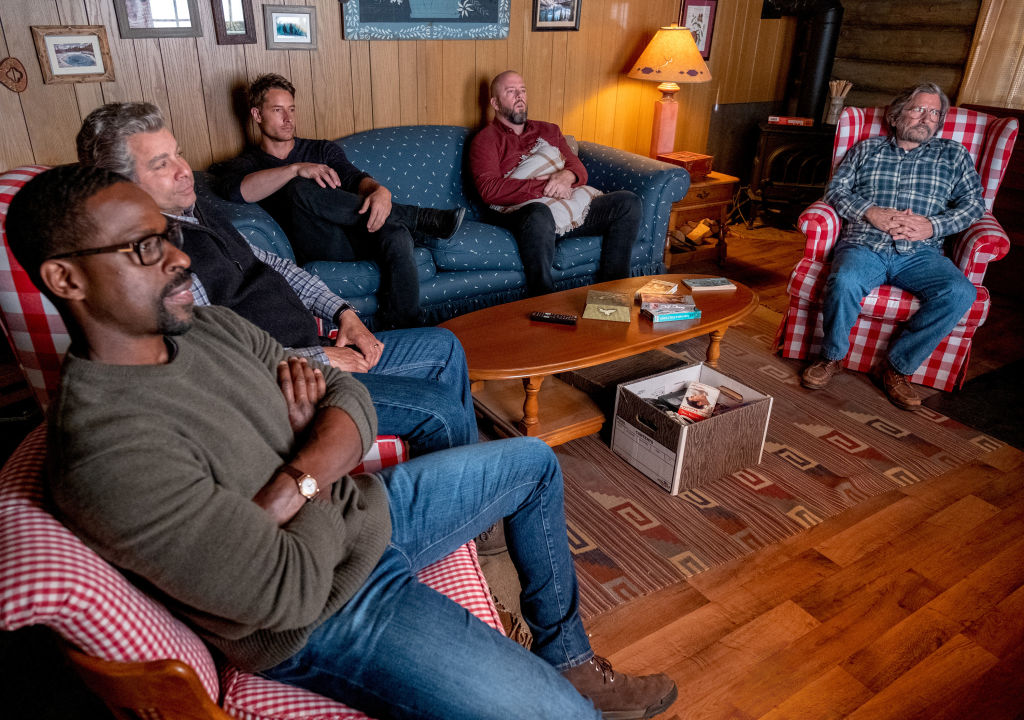 Sterling K. Brown as Randall, Jon Huertas as Miguel, Justin Hartley as Kevin, Chris Sullivan as Toby, Griffin Dunne as Nicky sit on a couch in the cabin watching TV on season 5 of 'This Is Us'.