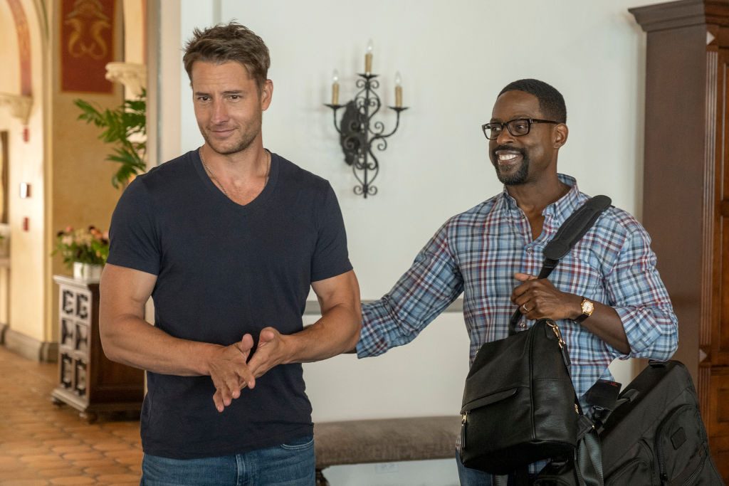 Justin Hartley as Kevin, wearing a dark v-neck tee, and Sterling K. Brown as Randall, wearing a blue plaid button-down,prepare for Kevin's wedding on 'This Is Us'