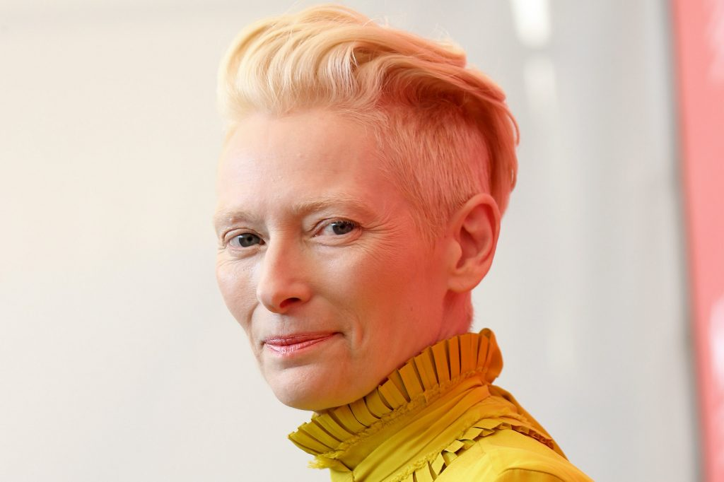 Tilda Swinton smiling in front of a white background