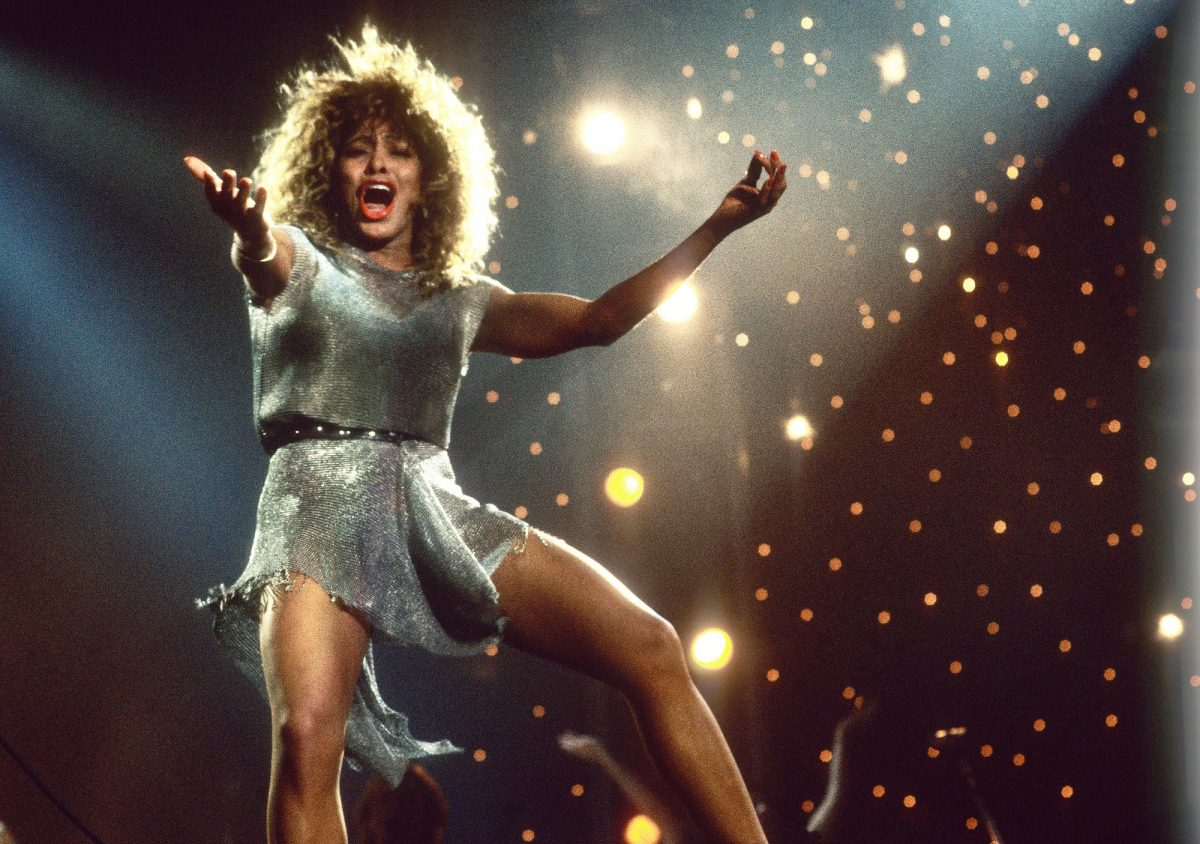 Tina Turner dances on stage in a silver dress