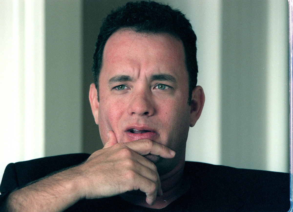 Tom Hanks rests his head on his hand thoughtfully during a Q&A session