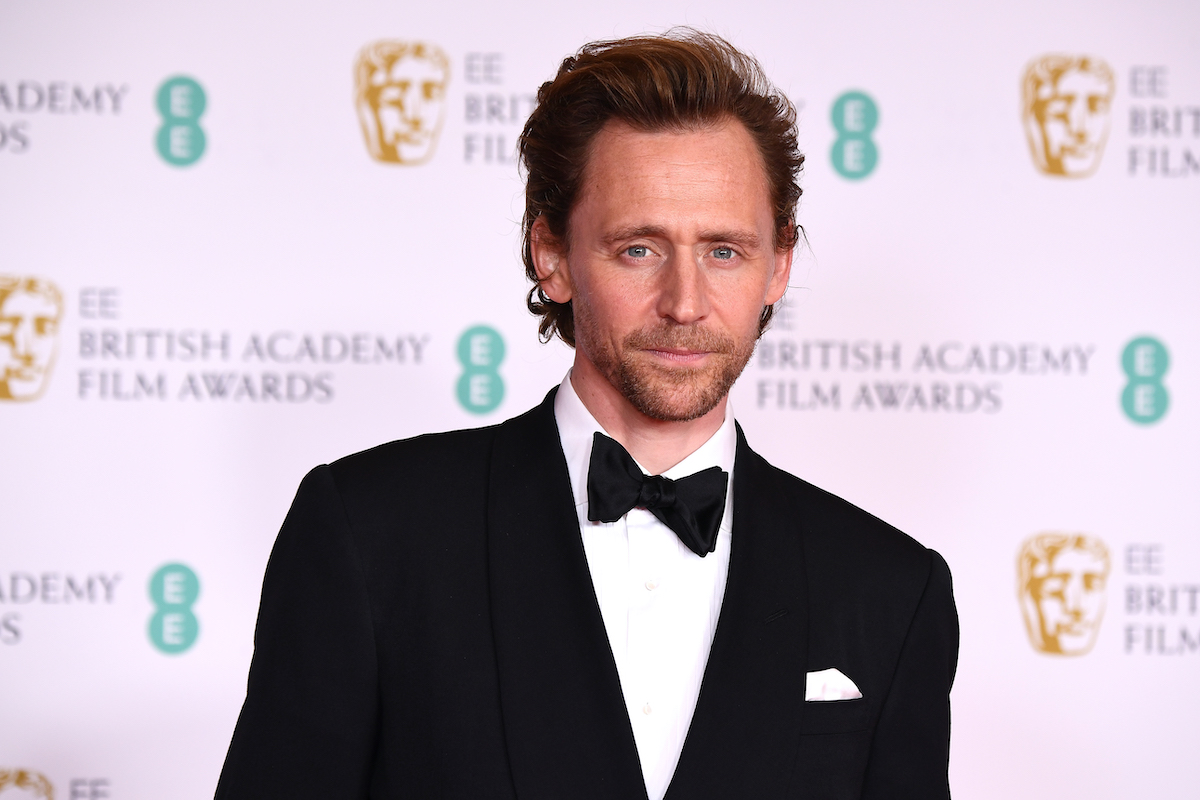 Tom Hiddleston wears a suit and poses at the EE British Academy Film Awards 2021