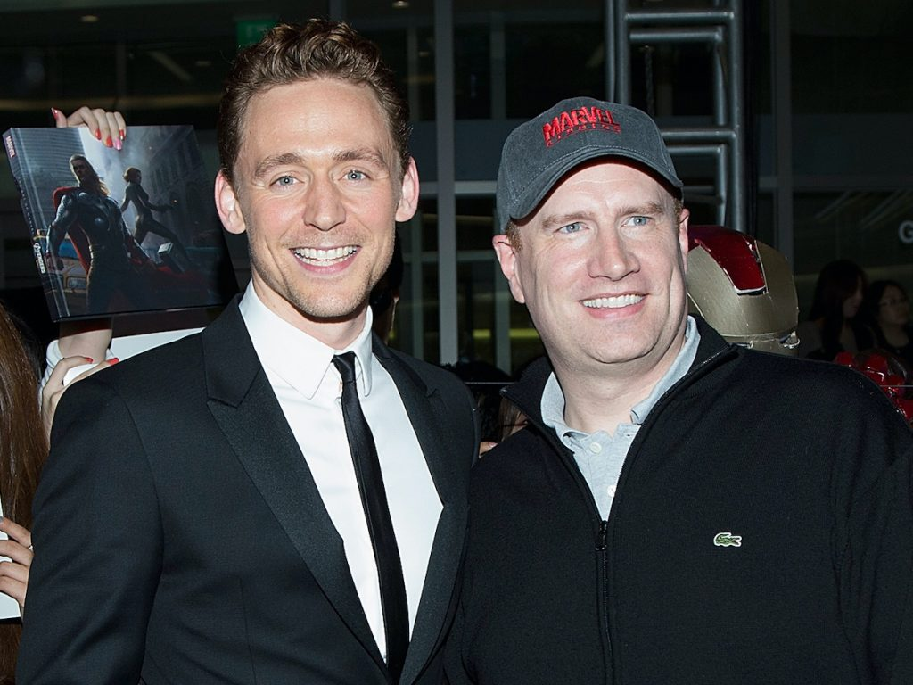 Tom Hiddleston smiles in a black suit and Kevin Feige smiles in a black quarter-zip and grey Marvel hat.